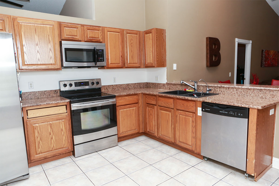 before picture of out of date kitchen with brown cabinets and brown granite countertops