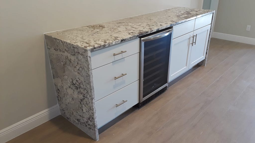 custom waterfall granite countertop sidebar with cabinets and wine cooler